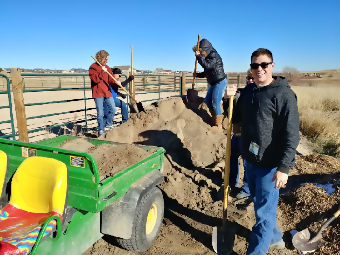(From left to right) Senior Master Sgt. Ruth Altman-Burnett, Staff Sgt. Gomez, Alba Palacio, Carri Boswell and Staff Sgt. Nikolaus Rouse spread fresh dirt on an out door riding coral at the Pikes Peak Therapeutic Riding Center, Nov. 30. The HQ RIO Detachment 3 staff spent the afternoon performing a variety of maintenance and housekeeping projects for the local non-profit.