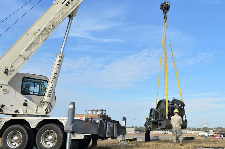 U.S. Airmen assigned to the 20th Civil Engineer Squadron guide a Barrier Artillery Kit-12 rotary friction brake aircraft arresting system as a crane lifts it at Shaw Air Force Base, S.C., Dec. 3, 2016. Airmen and contractors assigned to the 20th CES power production flight performed the replacement so the systems could be ready for inspection the following week. (U.S. Air Force photo by Airman 1st Class Christopher Maldonado)