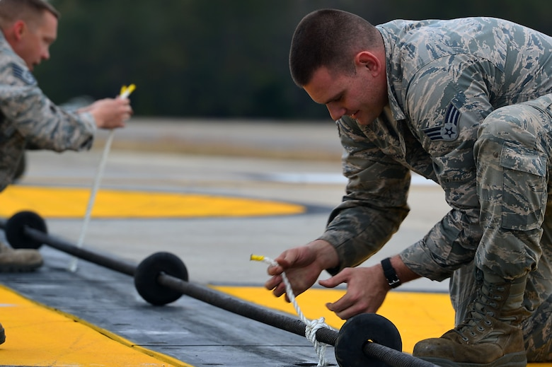 U.S. Air Force Senior Airman Jacob Smith, 20th Civil Engineer Squadron power production technician, prepares rubber donuts for a Barrier Artillery Kit-12 rotary friction brake aircraft arresting system cable at Shaw Air Force Base, S.C., Dec. 3, 2016. The rubber donuts elevate the cable to the proper height, providing proper distance for an aircraft to latch onto the cable in the event of an emergency landing. (U.S. Air Force photo by Airman 1st Class Christopher Maldonado)