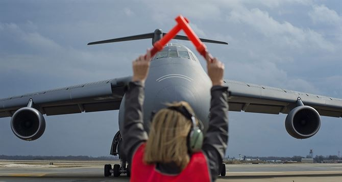 A member of the 512th Airlift Wing at Dover AFB, Delaware, guides the pilot of one of the wing's C-5 Galaxy aircraft. The 512th has teamed up with the active-duty 436th AW since the early 1970s to move troops and cargo around the globe. (Capt. Bernie Kale)