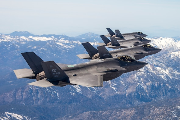 Flocking together: Three F-35As and an F-35C are pictured with the Sierra Nevada Mountains in the background during a recent four-ship test sortie conducted by the 461st Flight Test Squadron. Testing is done to ensure data is shared appropriately and accurately between aircraft. (Courtesy photo by Darin Russell/Lockheed Martin)