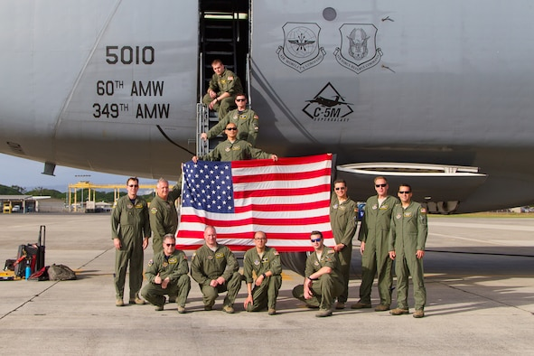 "A 312th Airlift Squadron aircrew from Travis Air Force Base, Calif., displays ""Old Glory"" upon delivering the flag to Joint Base Pearl Harbor-Hickam, Hawaii, Dec. 2, 2016.