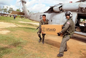A U.S. Navy sailor and an Armed Forces Philippines soldier unload a box of humanitarian aid from USAID on Panay Island, demonstrating interagency and international cooperation.