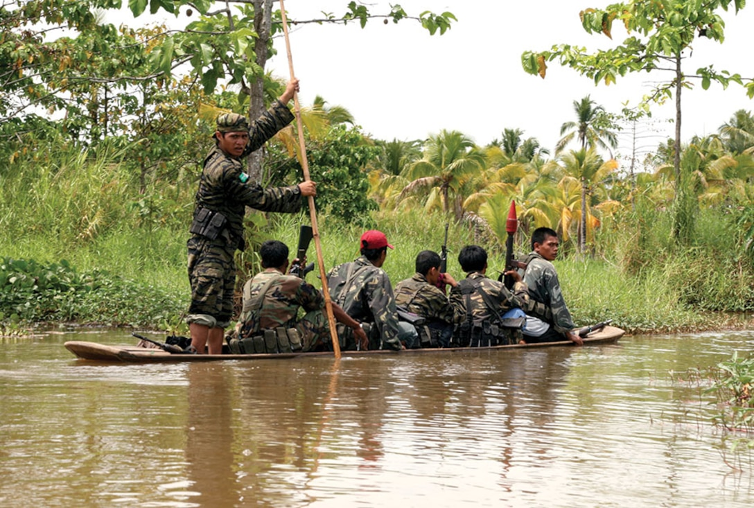 Moro Islamic Liberation Front members travel down a river in Maguindanao, Philippines.
