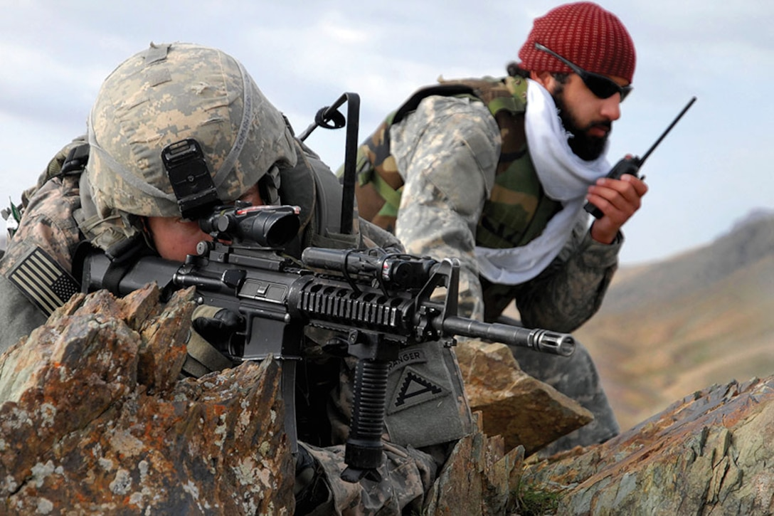 1st Lt. Jared Tomberlin, left, and an interpreter pull security on top of a mountain ridge during a reconnaissance mission near Forward Operating Base Lane in the Zabul province of Afghanistan.