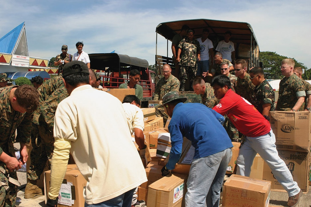 U.S. Marines, local residents and Philippine army soldiers work together to unload supplies in Operation Goodwill Delivery.