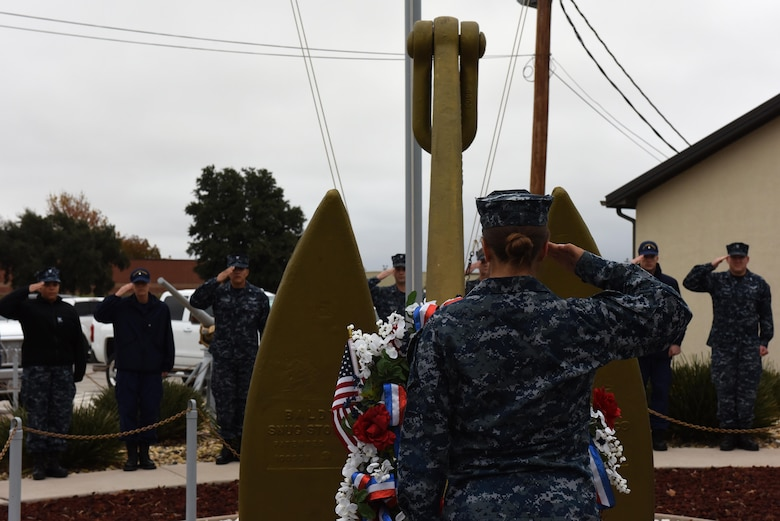 U.S. Navy sailors salute a memorial wreath during Taps for the 75th Pearl Harbor remembrance ceremony at Liberty Park on Goodfellow Air Force Base, Texas, Dec. 7, 2016. The wreath was placed out in the open for base members to observe. (U.S. Air Force photo by Airman 1st Class Caelynn Ferguson/Released)