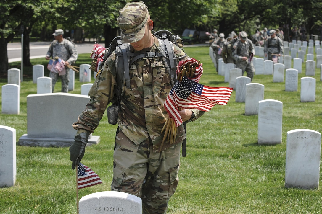 "Soldiers place American flags in front of headstones during ""Flags In"" at Arlington National Cemetery in Arlington, Va., May 26, 2016. DoD photo by Marvin D. Lynchard"