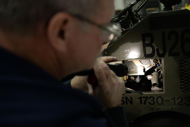 Department of the Air Force Robert Wurster, a 354th Maintenance Squadron aerospace ground equipment technician, inspects a MJ-1 bomb lift Dec. 5, 2016, at Eielson Air Force Base, Alaska. Wurster found and replaced a broken fuse which allowed the lift to continue operations. (U.S. Air Force photo by Airman Eric M. Fisher)