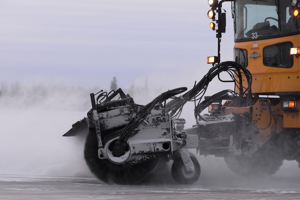 U.S. Air Force Airman Austin Oliver, a 354th Civil Engineer Squadron pavement and construction equipment operator, drives a snow broom to clear part of the flight line Dec. 1, 2016, at Eielson Air Force Base, Alaska. Eielson's Snow Barn clears snow and ice off the flight line to allow for continued operations. (U.S. Air Force photo by Airman Eric M. Fisher)