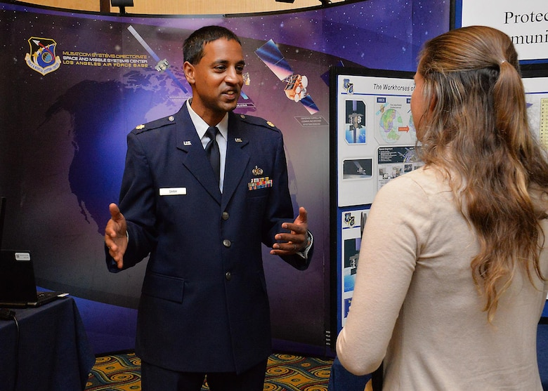 Maj. Anand Shah, deputy of the Advanced Extremely High Frequency space segment branch in SMC's Military Satellite Communications Directorate, discusses details of the MILSATCOM program with a prospective applicant during an Air Force Civilian Service Job Fair Nov. 16 at the Los Angeles Airport Marriott. The one-day job fair was hosted by Personnel from the Space and Missile Systems Center and Air Force Personnel Center.