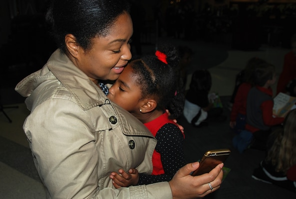 Akera Gamble embraces her daughter, Arielle, during a Facetime chat with her husband minutes before Arielle sings for attendees Dec. 7 at the annual McNamara Headquarters Complex tree lighting ceremony.