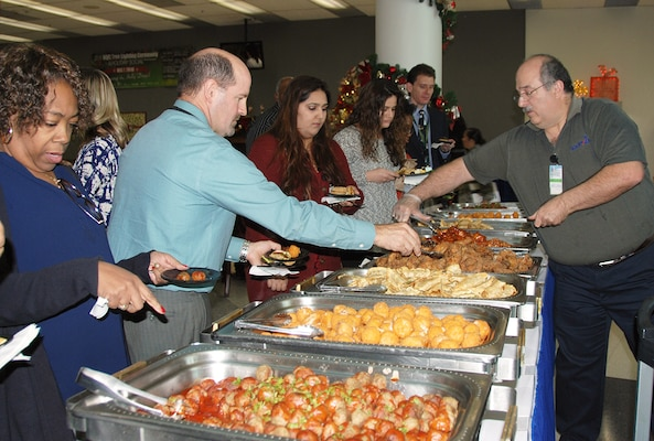 McNamara Headquarters Complex employees help themselves to free snacks at a holiday social following the annual HQC tree lighting ceremony Dec. 7.