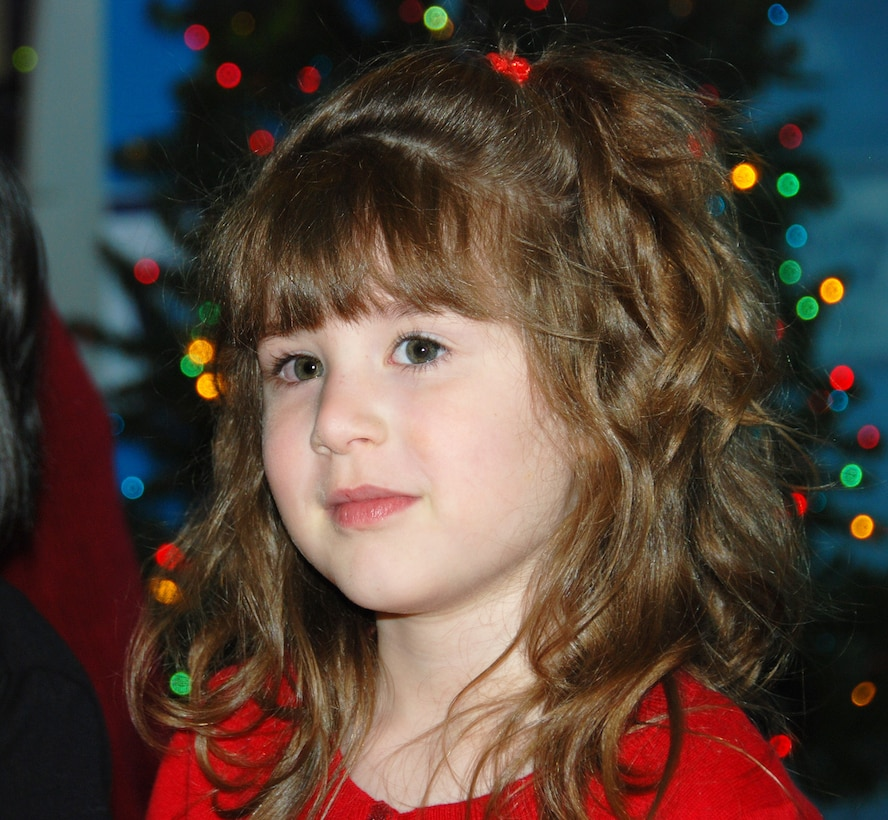 """Four-year-old Mary Baker pauses while shyly singing """"Santa Claus is Coming to Town"""" Dec. 7 at the McNamara Headquarters Complex. She and the rest of the HQC Child Development Center's pre-kindergarten class sang songs for those gathered at the annual HQC tree lighting ceremony."""