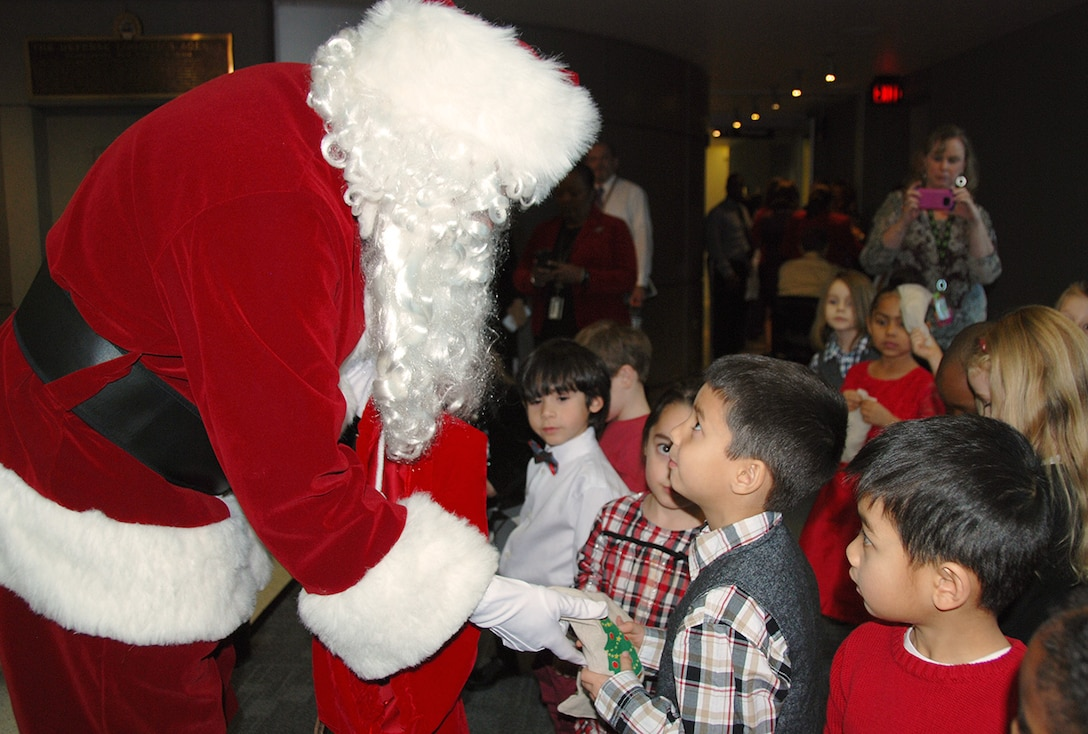 Pre-kindergarteners from the McNamara Headquarters Complex Child Development Center look at Santa Claus in awe while parents capture the moment taking cell-phone pictures.