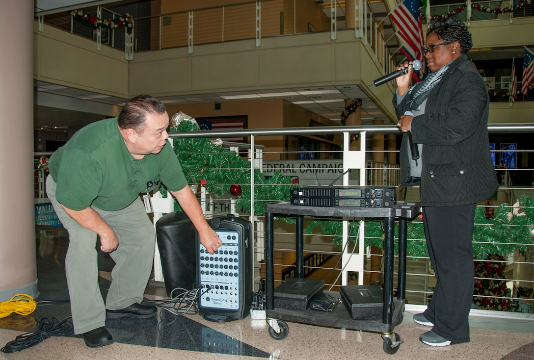 Multimedia specialists Vincent Mundo (left) and Devetrias Johnson (right) set up a sound system so employees hugging the rails on all five floors of the McNamara Headquarters Complex can hear the music and guest speakers during the annual HQC tree lighting ceremony Dec. 7.