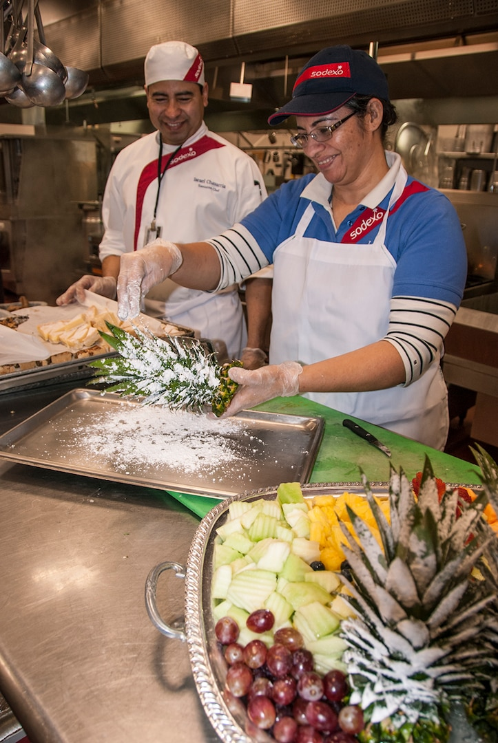 Lety Flores (right) sprinkles powdered sugar over a pineapple top for a snowy effect as Israel Chavarria (left) watches at the McNamara Headquarters Complex Dec. 7. Her creation will serve as a garnish on complementary fruit and cookies trays available during a holiday social following the annual HQC tree lighting ceremony.