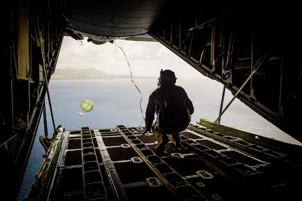 Airman 1st Class Alejandra Vargas, 36th Airlift Squadron C-130 Hercules loadmaster, pushes a bundle during Operation Christmas Drop at Andersen Air Force Base, Guam, Dec. 5, 2016. Australian and Japanese aircrews joined U.S. Airmen to execute the Humanitarian Aid/Disaster Relief training event where C-130 aircrews perform low-cost, low-altitude airdrops to drop zones while providing critical supplies to 56 islands. (U.S. Air Force photo by Senior Airman Delano Scott/Released)