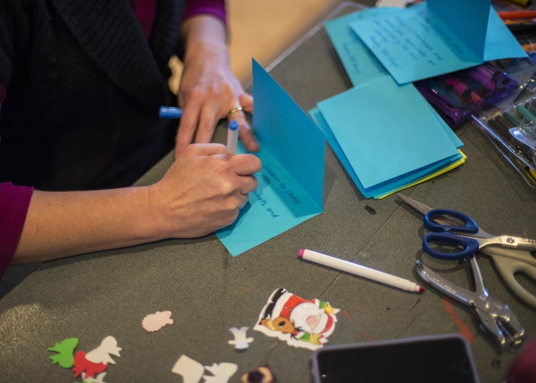 A volunteer crafts a handmade card, to adorn a package of cookies, for Holloman's annual Airman Cookie Drive at the Community Activity Center at Holloman Air Force Base, N.M. on Dec 5, 2016. Cookie drive volunteers collected cookies from donors, organized cookies according to type, dispersed cookies into individual paper bags, and attached handmade cards to each bag of cookies. (U.S. Air Force photo by Airman 1st Class Alexis P. Docherty)