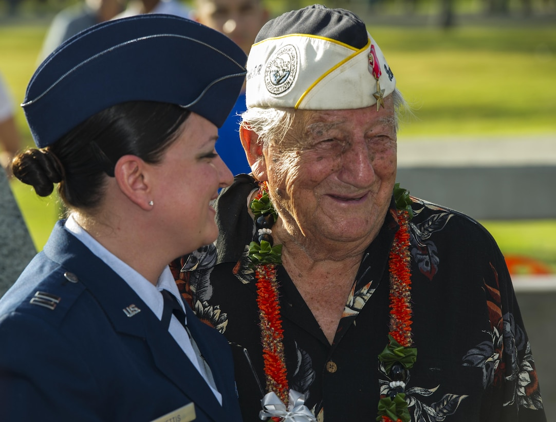 Capt. Kimber Nettis, 515th Air Mobility Operation Wing Cyberspace Operations chief, smiles with Command Sgt. Maj. Armando Galella, a veteran who lost his best friend during the Dec. 7, 1941 attacks on Oahu, during a photo-opportunity session after the 75th Commemoration of the Dec. 7, 1941 attack on Hickam Field ceremony Dec. 7, 2016, at Joint Base Pearl Harbor-Hickam, Hawaii. The attacks on seven bases throughout Oahu precipitated America's entry into World War II, and the annual commemoration ceremony is designed to foster reflection, remembrance, and understanding for those affected by the events that took place 75 years ago. (U.S. Air Force photo by Tech. Sgt. Nathan Allen)