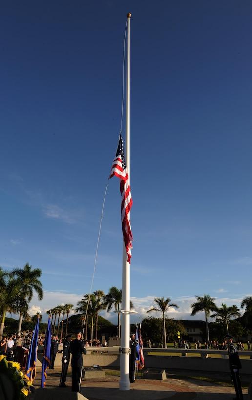 Members of the Hickam Honor Guard raise the American flag to half-mast at the 75th Commemoration of the Dec. 7, 1941 attack on Hickam Field ceremony  Dec. 7, 2016, at Joint Base Pearl Harbor-Hickam, Hawaii. The attacks on seven bases throughout Oahu precipitated America's entry into World War II, and the annual commemoration ceremony is designed to foster reflection, remembrance, and understanding for those affected by the events that took place 75 years ago. (U.S. Air Force photo by Tech. Sgt. Nathan Allen)