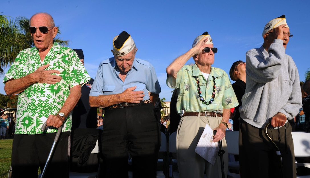 Survivors of the attacks on Pearl Harbor Naval Station and Hickam Field stand during the singing of the national anthem during the 75th Commemoration of the Dec. 7, 1941 attack on Hickam Field ceremony  Dec. 7, 2016, at Joint Base Pearl Harbor-Hickam, Hawaii. The attacks on seven bases throughout Oahu precipitated America's entry into World War II, and the annual commemoration ceremony is designed to foster reflection, remembrance, and understanding for those affected by the events that took place 75 years ago. (U.S. Air Force photo by Tech. Sgt. Nathan Allen)