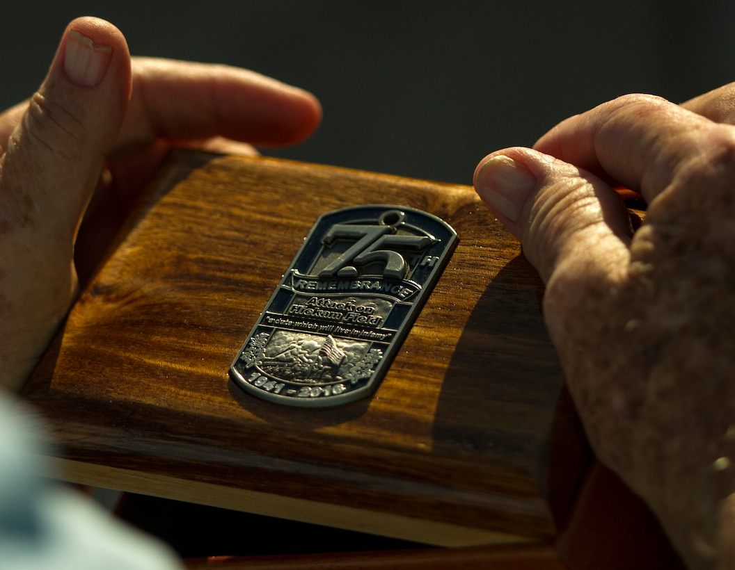 U.S. Army Private Edward Bloch, a survivor of the attack on Hickam Field, holds a wooden box given to him during the 75th Commemoration of the Dec. 7, 1941 attack on Hickam Field ceremony Dec. 7, 2016, at Joint Base Pearl Harbor-Hickam, Hawaii. Bloch was a switchboard operator in the control tower assigned to the 5th Bomb Group at Hickam Field. During the attack, he made eye contact with a Japanese aircraft gunner and recalls the Star Spangled Banner being played over the public announcement system between the two waves of attacks. After the attack, Bloch served in the South Pacific Flying Combat crew in the B-17 Flying Fortress and B-24 Liberator Bombers. (U.S. Air Force photo by Tech. Sgt. Nathan Allen)