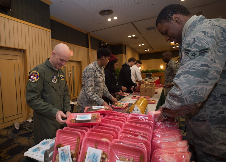 U.S. Air Force Col. R. Scott Jobe, 35th Fighter Wing commander, assists Airmen package cookies during the annual Cookie Caper event at Misawa Air Base, Japan, Dec. 7, 2016.  Preparation began two days prior when volunteers baked donated dough at the Commissary and collected baked cookies from around the Misawa community for packaging. (U.S. Air Force photo by Senior Airman Deana Heitzman)