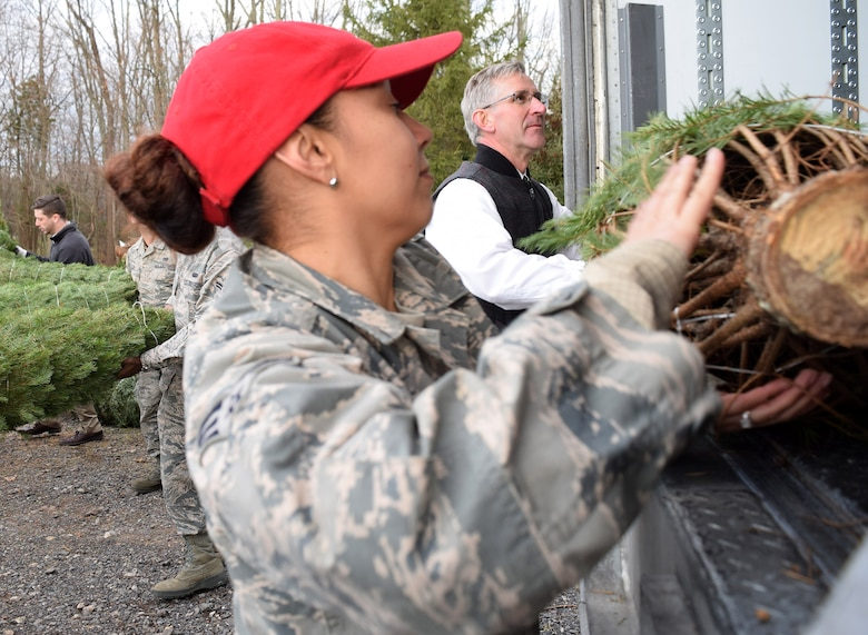 Senior Airman Ramona Navarro, heavy equipment mechanic with the 201st Rapid Engineer Deployable Heavy Operational Repair Squadron Engineer Squadron, Det. 1. teams with Pa. Secretary of Agriculture, Russell Redding to load nearly 100 Christmas trees during the kickoff of the Trees for Troops program at Bustard's Tree Farm in Lansdale, Pa. on Dec. 2, 2016. The project's goal is to help provide holiday memories to military members and their families across the U.S. and abroad. (U.S. Air National Guard photo by Master Sgt. Christopher Botzum)