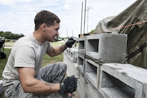 U.S. Air Force Airman 1st Class Daniel Davis, 18th Civil Engineer Squadron structural apprentice, checks the evenness of a brick wall Dec. 7, 2016, at Kadena Air Base, Japan. Using a level, structural apprentices ensure a wall will be built evenly and will be strong enough to have structural integrity. (U.S. Air Force photo by Senior Airman Lynette M. Rolen/Released)