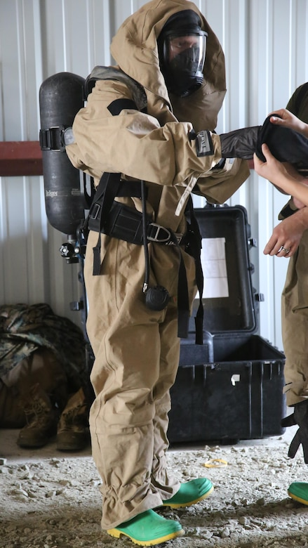 A Marine suits-up in his Assessment Consequence Management gear during a field exercise at Marine Corps Outlying Field Atlantic, N.C., Nov. 30, 2016. Twenty-two Marines with Chemical, Biological, Radiological and Nuclear Defense, 2nd Marine Aircraft Wing, conducted a week-long annual training exercise to refresh the defense specialists on the roots of their basic military occupational specialty training. The exercise included an assortment of stations and classes that tested the Marines physically and mentally, including {put the things it included here}. (U.S. Marine Corps photo by Lance Cpl. Mackenzie Gibson/Released)