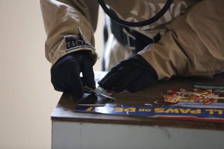 A Marine completes a puzzle to test his dexterity during a field exercise at Marine Corps Outlying Field Atlantic Nov. 30, 2016. Twenty-two Marines with Chemical, Biological, Radiological and Nuclear Defense, 2nd Marine Aircraft Wing, conducted a week-long annual training exercise that refreshed the defense specialists on the roots of their basic military occupational specialty training. The exercise included an assortment of stations and classes that tested the Marines physically and mentally. (U.S. Marine Corps photo by Lance Cpl. Cody Lemons/Released)