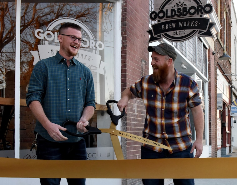 U.S. Air Force veterans Carson Clark (left) and Zac Fein (right) cut a ribbon for the grand opening of their, Dec. 2, 2016, in Downtown Goldsboro, North Carolina. Fein and Clark both finished their enlistment at Seymour Johnson Air Force Base, North Carolina as F-15E Strike Eagle crew chiefs assigned to the 4th Aircraft Maintenance Squadron. (U.S. Air Force photo by Airman Miranda A. Loera)