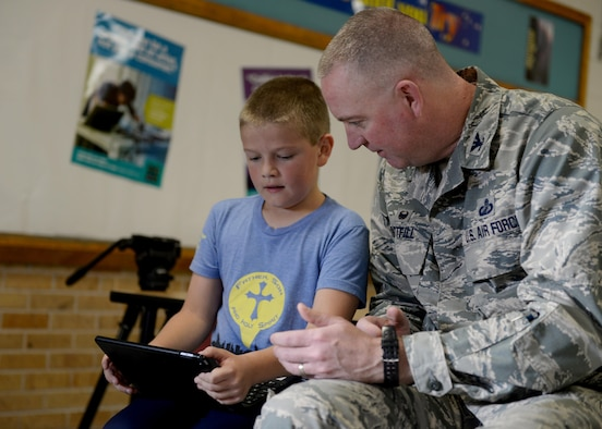 U.S. Air Force Col. Lance Whitfill, 97th Mission Support Group commander, looks on as a student controls a robot, December 6, 2016, Altus Air Force Base, Oklahoma. The STEM initiative hopes to inspire the next generation to take an interest in science, technology, engineering and mathematics. (U.S. Air Force Photo by Airman Jackson N. Haddon/Released).