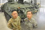 Army Pfc. Sam and Pvt. Jennifer Mei, both Pennsylvania Army National Guardsmen, pose in front of a Stryker armored fighting vehicle at the Ordnance School at Fort Lee, Va., Nov. 17, 2016. Sam graduated from the 17-week course Nov. 22, while Jennifer is scheduled to complete the course in March. Another sibling, 19-year-old Milton, is also undergoing training at Fort Lee as a student in the Petroleum Supply Specialist Course taught by the Quartermaster School. Army photo by Terrance Bell