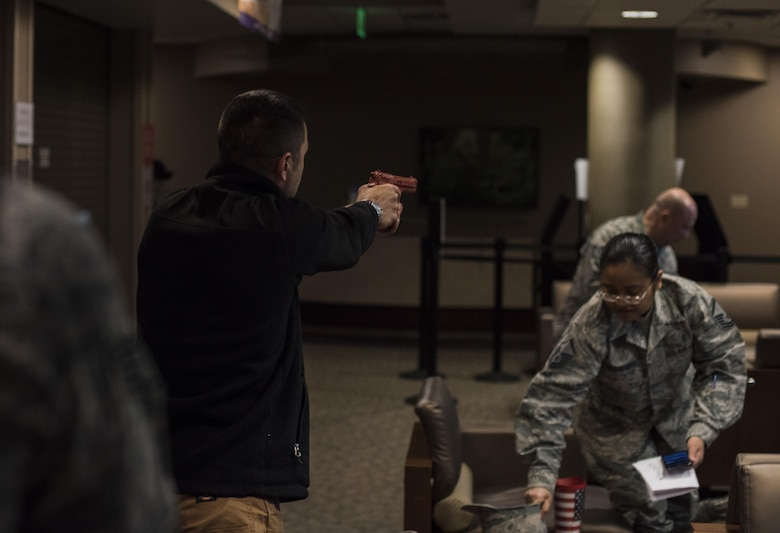 Master Sgt. Jeremy Utphall, 2nd Bomb Wing Inspector General exercise division superintendent, aims a training weapon at Airmen during an active shooter exercise at Barksdale Air Force Base, La., Nov. 29, 2016. Like an actual active shooter incident, Airmen weren't given a warning. While some were caught off guard, others implemented their training and avoided Utphall as he searched the medical building for victimes. (U.S. Air Force photo/Senior Airman Damon Kasberg)