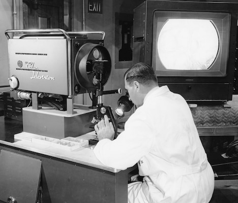 Lt. Col. Helmuth Sprinz, a surgical patholisgist at Walter Reed Army Medical Center, operates a color television microscope, designed by WRAMC and RCA technicians in 1957.