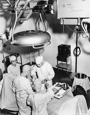 Color television cameras first entered the operating rooms of Walter Reed Army Medical Center, or WRAMC, which was then located in Washington, D.C., in 1957. The camera is trained on the surface of a mirror suspended at an angle above the operating table.