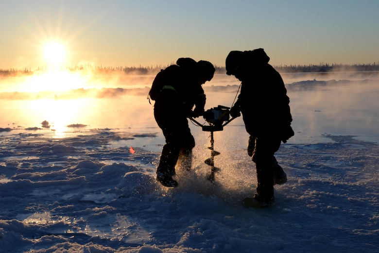 U.S. Air Force Senior Airman Carlos Aleman, a 354th Civil Engineer Squadron range maintenance technician, uses an auger to drill a hole in the frozen Tanana River with Tech. Sgt. Craig Slaten, the 354th CES noncommissioned officer in charge of service contracts, Dec. 5, 2016, in Fairbanks, Alaska. Slaten and Aleman use the auger to drill into the ice, exposing water which will build up the ice and create a stable bridge for transportation of equipment and supplies. (U.S. Air Force photo by Airman 1st Class Cassandra Whitman)