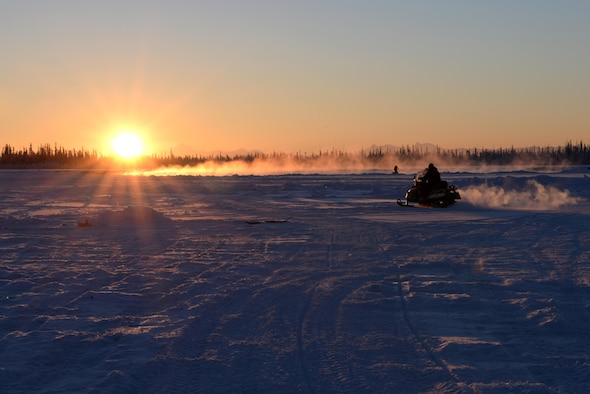 U.S. Air Force Airmen from the 354th Civil Engineer Squadron use snow machines to get across the ice bridge leading to the Blair Lakes Range Maintenance Complex Dec. 5, 2016, in Fairbanks, Alaska. The 354th CES Airmen build up the ice bridge across the Tanana River every two years to aid in the mission of the Airmen who maintain the maintenance range and equipment. (U.S. Air Force photo by Airman 1st Class Cassandra Whitman)