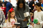 First Lady Michelle Obama helps Lauren Gordon, 9,  figure out where to put a toy during the Toys for Tots event at Joint Base Anacostia-Bolling, Washington, D.C., Dec. 7, 2016. DoD photo by Scott Pauley