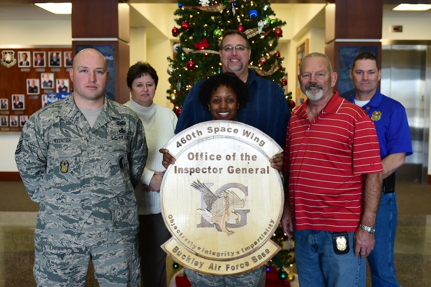 Members of the 460th Space Wing Inspector General office display their shield Dec. 8, 2016, on Buckley Air Force Base, Colo. The IG staff works directly with the commander to ensure the efficiency of the base and the welfare of the Airmen. (U.S. Air Force photo by Airman Jacob Deatherage/Released)