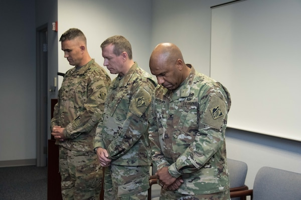 Col. Patrick Kinsman, commander of the U.S. Army Corps of Engineers, Middle East District, Maj. Gen. Robert Carlson, commanding general of USACE Transatlantic Division and Col. Vincent Quarles, outgoing commander of the Middle East District, bow their heads in prayer during the District's change of command ceremony at MED headquarters in Winchester, Va. Dec. 8.