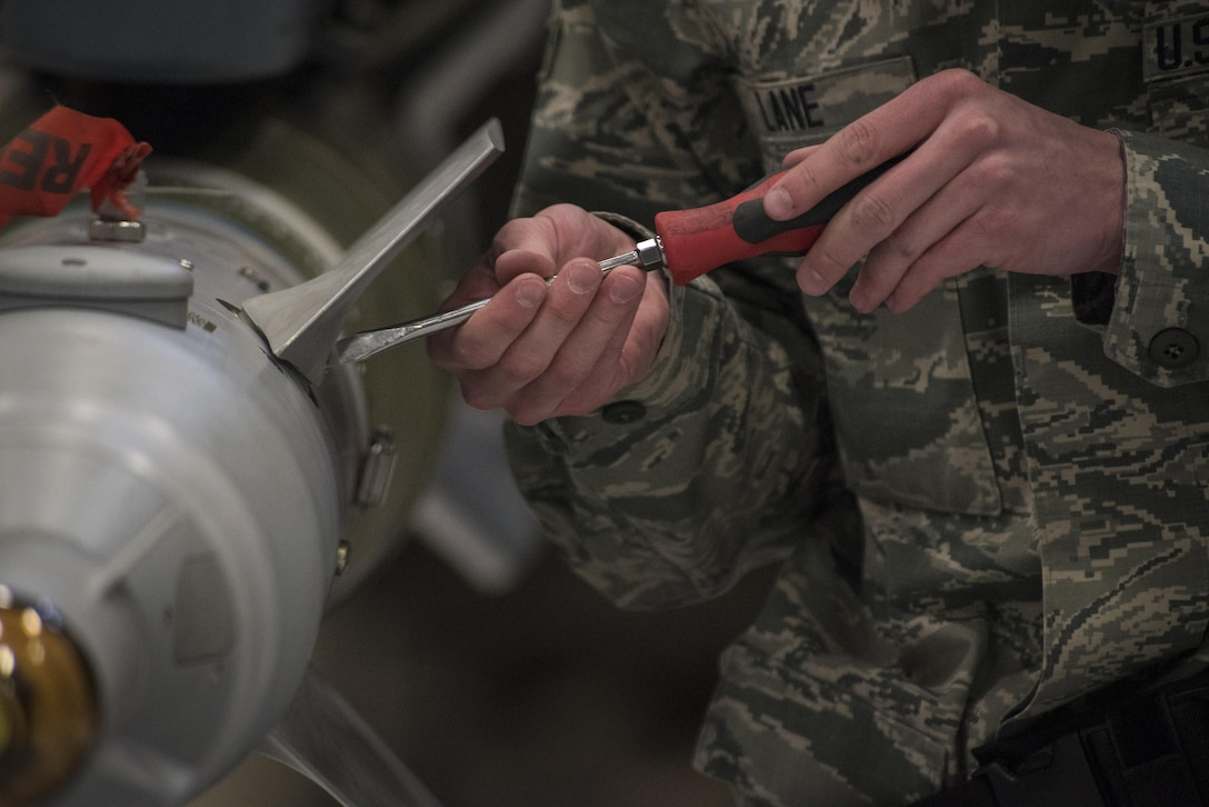 U.S. Air Force Airman 1st Class Duane Lane, 27th Special Operations Maintenance Squadron weapons load technician, secures an inert weapon into place for a weapons load competition Dec. 2, 2016, at Cannon Air Force Base, N.M. The competition tests weapons load crews' proficiency, reliability and speed. (U.S. Air Force Photo by Senior Airman Shelby Kay-Fantozzi/released)