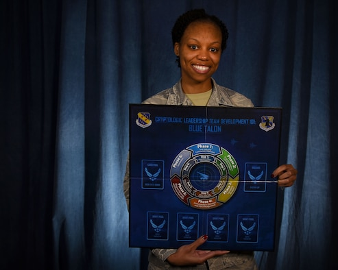 Staff Sgt. Monique McCoy, 70th Operations Support Squadron, wing mission training flight program manager, holds the board game portion of the Blue Talon training program. The mission training flight worked with a contractor to develop a program that could enable signals intelligence Airmen to gain an air operations mindset. (U.S. Air Force photo/Tech. Sgt. Veronica Pierce)