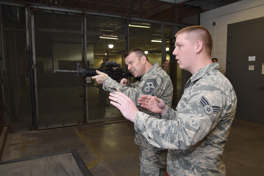 Air Force Sustainment Center Command Chief Master Sgt. Gary S. Sharp holds an M4 rifle while Senior Airman James Brewer, 72nd Logistics Readiness Squadron weapons custodian, provides guidance on how to properly line-up the laser sight during a mission and capabilities immersion tour with the 72nd Air Base Wing Dec. 7, 2016, Tinker Air Force Base, Okla. During his visit to the 72nd ABW CMSgt. Sharp learned about high-profile shops like finance and the ID card section while also learning about the lesser known shops like the mobility weapons vault operated by the 72nd LRS. (U.S. Air Force photo/Greg L. Davis)