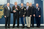 Frank Kendall, undersecretary of defense for acquisition, technology and logistics, left, presents members of the Special Operations Forces Acquisition, Technology, and Logistics Center of Special Operations Command with a Bronze Award during a ceremony at the Pentagon in Arlington, Va. Dec. 8, 2016. Standing with them on the Pentagon Hall of Heroes stage are Gen. Paul J. Selva, vice chairman of the Joint Chiefs of Staff, right, and Deputy Secretary of Defense Bob Work. DoD photo by EJ Hersom.