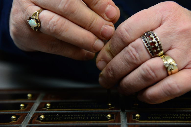 Sherry Pschernig, 341st Force Support Squadrons Arts and Crafts Center engraver, screws down a name plate Dec. 7, 2016, at Malmstrom Air Force Base, Mont. Pschernig is one of two individuals who work in the shop, where they make the majority of their products from scratch, to include wooden plaques, trophies and awards. (U.S. Air Force photo/Airman 1st Class Magen M. Reeves)