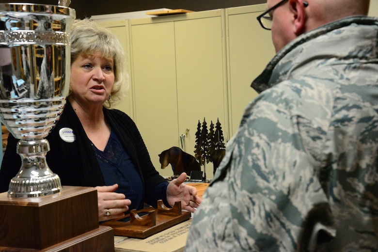 Sherry Pschernig, 341st Force Support Squadrons Arts and Crafts Center engraver, assists a customer Dec. 7, 2016, at Malmstrom Air Force Base, Mont. The Engraving Shop has the capability to make products from scratch to include wooden plaques, engraved glasses, acrylic, trophies, awards or knives to fit any customer's needs. (U.S. Air Force photo/Airman 1st Class Magen M. Reeves)