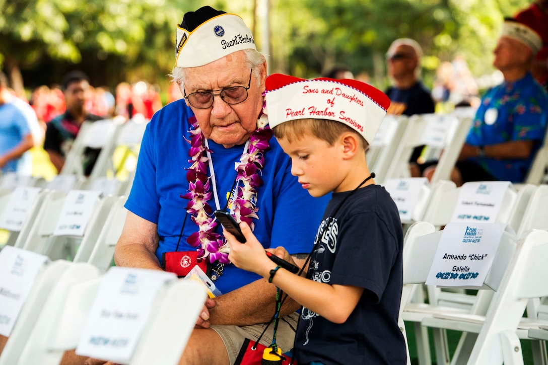 A child teaches Pearl Harbor survivor Lester  Lindow how to use modern technology